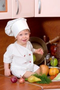 Small boy sitting on a counter wearing a chef's hat